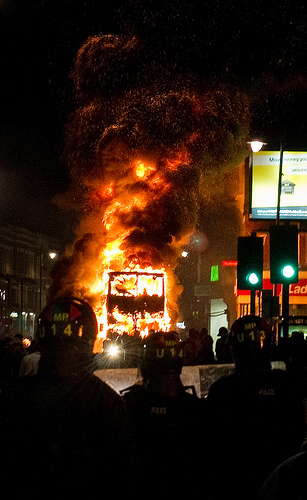 A double decker bus burns as riot police look on